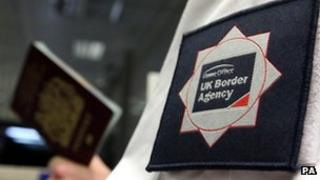 UK Border Agency officer holding passport
