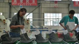 A picture taken on April 19, 2012 shows people working on the assembly line at Huajian shoe factory in Dukem, Ethiopia.