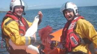 Helmsman Billy McAndrew holding Janet the gannet after crew member Thomas Wibberley removed the bag Pic: Kinghorn RNLI Lifeboat