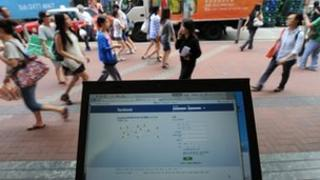 Facebook on a phone with crowd of Chinese people behind