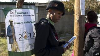 """A woman stands near an election poster in Maseru on May 24, 2012 two days ahead of the southern African state of Lesotho""""s parliamentary elections."""