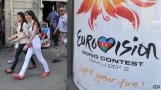 Women walk past a sign for Eurovision 2012