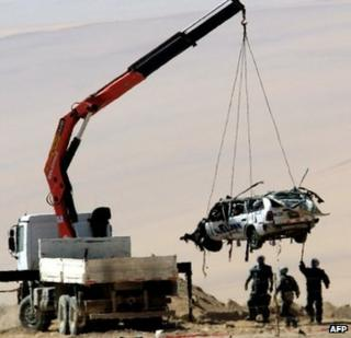 Recovery vehicle lifts Peruvian car destroyed by landmine in Chile