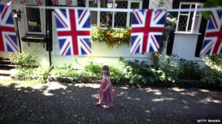 girl walks past house with union flags hanging down in front