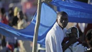 Haitian man holds a child in makeshift camp after the 2010 earthquake