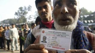 Bangladeshi man holds up a national identity card