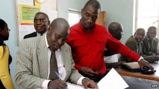 Andrew Banda (in the red shirt), eldest son of the former Zambian president Rupiah Banda, being charged in a police station