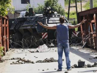 A man faces a German K-For armoured car on a bridge in Rudare, Kosovo, 1 June