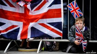 Young boy waits in the crowd with a flag prior the arrival of Queen Elizabeth II for a visit to Exeter city centre on May 02, 2012