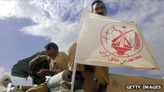 An MEK member displays the group's flag