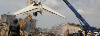 People watch as a crane lifts the tail of a plane after it crashed at Iju-Ishaga neighbourhood in Lagos 4 June 2012