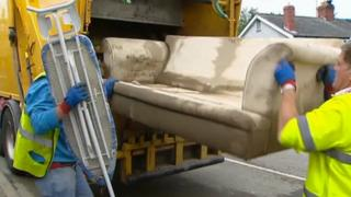 A sofa is put into the back of a rubbish truck