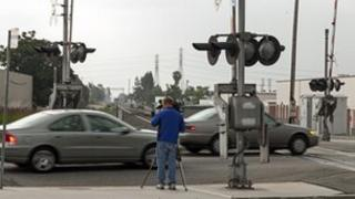 A television cameraman tapes the traffic crossing in the San Gabriel area of Los Angeles where Secretary of Commerce John Bryson is alleged to have crashed