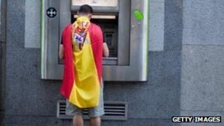 Man draped in Spanish flag withdraws cash from an ATM