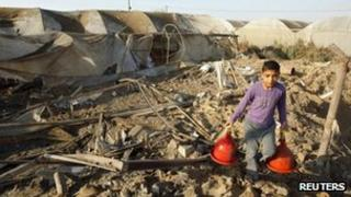 A Palestinian boy carries chicken waterers found in a coop as he walks over debris at the site of an Israeli air strike in Rafah in the southern Gaza Strip on 6 June 2012