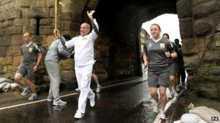 A torchbearer carries the Olympic flame under a bridge
