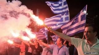 Greeks in Athens with flags and flares