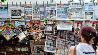 A woman reads newspapers' headlines in Athens