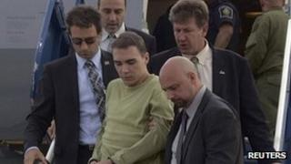 Luka Rocco Magnotta is escorted off a plane in Mirabe by police