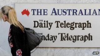A woman walks past a sign outside the entrance to the News Limited building in Sydney on 20 June 2012