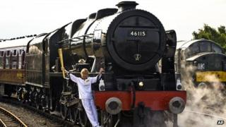 Torchbearer Josephine Loughran carrying the Olympic Flame on the Scots Guardsman steam locomotive