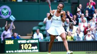 """Heather Watson smiling on Wimbledon centre court with sign saying """"102mph"""" behind her"""