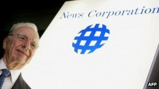Rupert Murdoch in front of News Corp logo