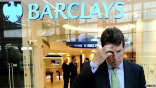 Man scratching his head in front of Barclays sign