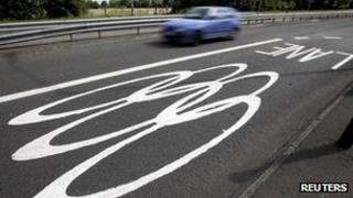 A car passes Olympic traffic lanes markings on a road near Egham south-west of London