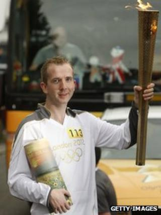 Mark Reynolds holds the ashes of his brother and originally nominated Torchbearer, David during the relay