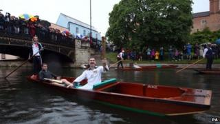 Torchbearer carrying Olympic flame on a punt