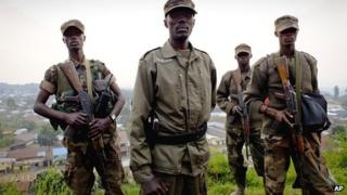 Col Makenga (centre) commander of the M23 rebel movement, stands on a hill overlooking the border town of Bunagana, DR Congo, Sunday 8 July 2012