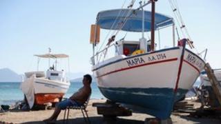 Man sits in shade of boat on Greek island.