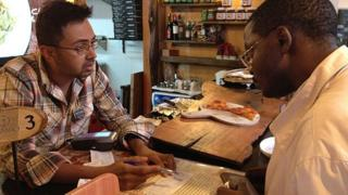Mambo Pizza's Nish Shah explains to a customer how to check in using the NikoHapa service using his mobile phone