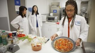 Senior research scientist Maya Cooper shows a vegan pizza developed at NASA's Advanced Food Technology Project.