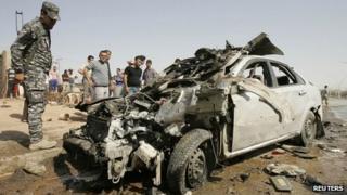 Iraqi policeman looks at car wrecked by bombing in Kirkuk (23/07/12)
