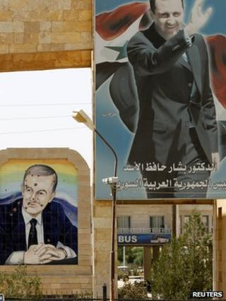 Portraits of Syrian President Bashar al-Assad (top) and his father former Syrian President Hafez al-Assad (rear) are seen at the Rabia border crossing between Iraq and Syria (23 July 2012)