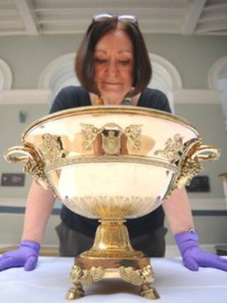 Assistant Curator Alison Patterson with a punch bowl created for the Emperor Napoleon