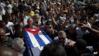 Friends and family of Cuban activist Oswaldo Paya carry his coffin during his burial at a cemetery in Havana