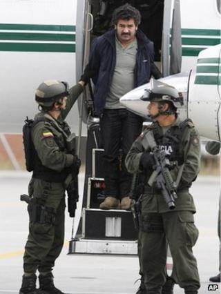 Diego Perez Henao, better known as Diego Rastrojo, is escorted off a plane at Bogota airport