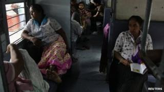 Passengers sit in a train as they wait for electricity to be restored at a railway station in the northern Indian city of Allahabad July 30, 2012.