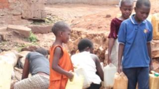 Children in Uganda carry water