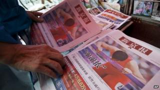 A man picks copies of the Beijing News newspaper at a newsstand, where Chinese hurdler Liu Xiang's photos are seen on local papers' front pages, in central Beijing, 8 Aug 2012