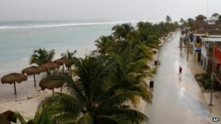 A man walks in a nearly deserted street Mahahual, Mexico, Tuesday, 7 August, 2012