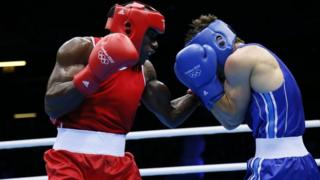 Cameroon's boxer Serge Ambomo in an Olympic boxing match (left)