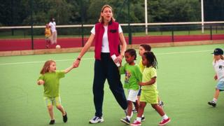 lady with primary school children on field