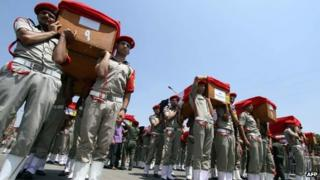 Egyptian soldiers carry the coffins of their comrades killed in an attack in Sinai during their funeral in Cairo on August 7, 2012.