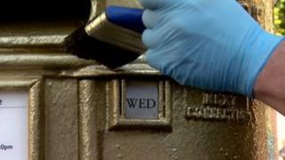 Man paints a post box gold