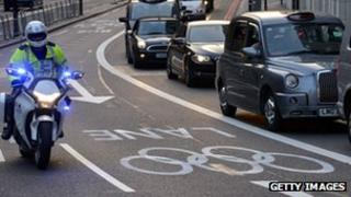 A police motorcyclist rides in a reserved Games Lane as taxis and commuters queue to leave central London