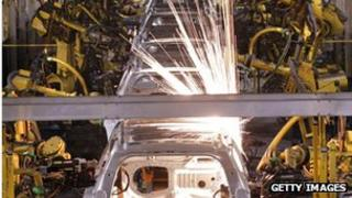 A crossover SUV vehicle is welded by robot arms as it goes through the assembly line at the General Motors Lansing Delta Township Assembly Plant